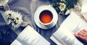 books and a cup of tea kept on a bed