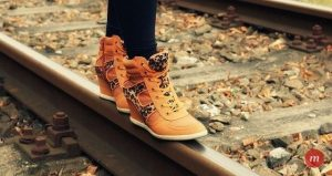 girl wearing orange color shoes walking on a rail track